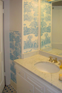 Carrera marble countertops and Toile wallpaper in a lovely blue and white update this charming bathroom with it's original black and white mosaic tile floor.